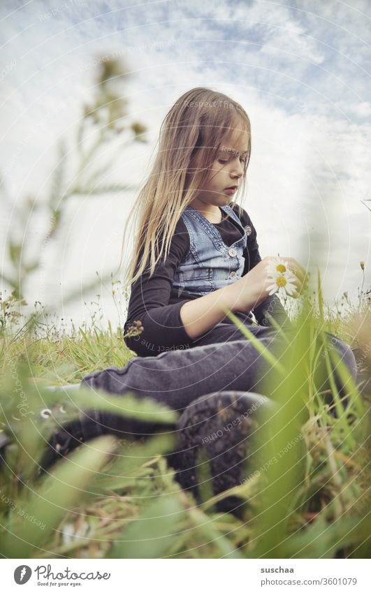 girl sits in a flower meadow and makes a chain of flowers (which can only be seen vaguely) Infancy Cool-headed Meditative Grass Flower meadow Meadow