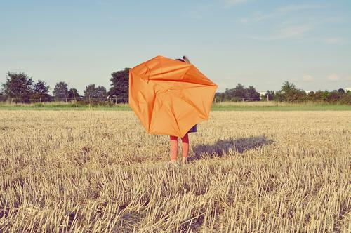 child on a straw chopper with a broken umbrella Child Umbrella Broken Orange acre Field straw field Grain field Agriculture Landscape arable farming Summer
