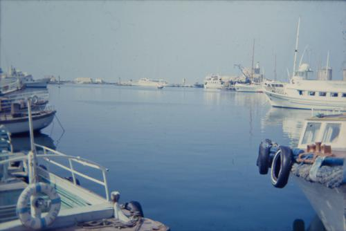 old slide of a marina somewhere in greece Old Retro Slide 70s Ocean Water Blue ägais Greece Harbour boats ships Mooring place Floating tyres Life belt Car tire