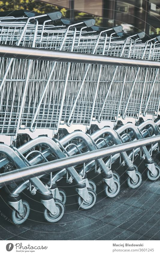 Row of empty shopping carts. supermarket retail row trolley store buy basket business grocery consumerism metallic purchase chrome object concept line symbol