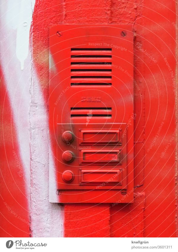 Bell plate with three bells and intercom system completely sprayed red Red Graffiti Exterior shot Name plate Intercom system White Colour photo Wall (building)