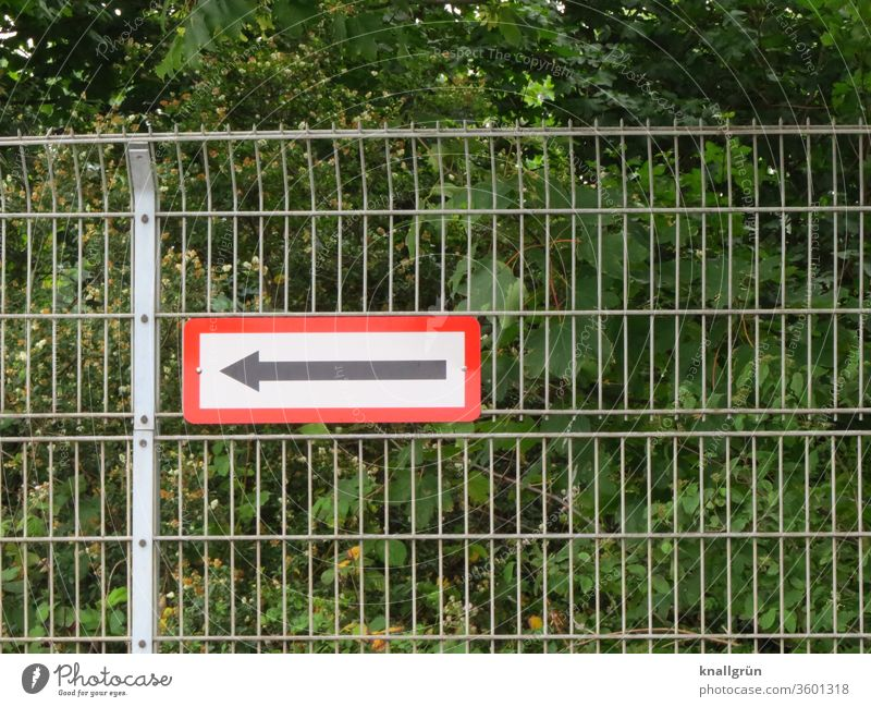 Grid fence with sign with arrow pointing to the left. In the background green bushes and trees. Arrow Fence Signs and labeling Signage Direction Orientation