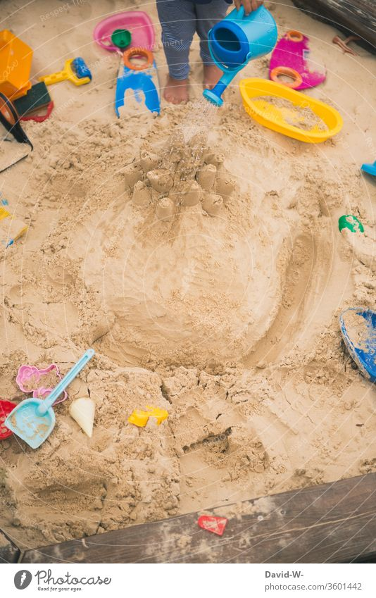 Child playing in the sandbox plays Sandpit Toys fun Joy self-employment Employment Anonymous Cast Water Wet Watering can sandy Garden Playground Playing