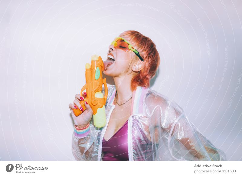 Retro futuristic woman licking water gun style eyes closed young weapon outfit retro female model dyed hair trendy jacket sunglasses pistol angry vintage