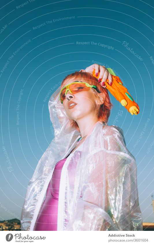 Retro futuristic female with water gun looking at camera woman success arm raised sky style young retro scream outfit model dyed hair trendy win yell shout