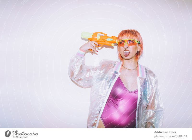 Funny retro futuristic woman pointing pistol at head gun style show tongue funny young weapon outfit female model water toy dyed hair trendy shoot jacket