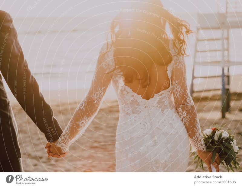 Happy newlyweds on sunny beach couple wedding happy celebrate groom bride sunset bouquet dress elegant suit classy romantic love marriage together style