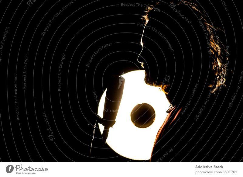 Silhouette of male singer in studio man microphone musician dark silhouette skill creative talent lamp light luminous illuminate perform professional entertain