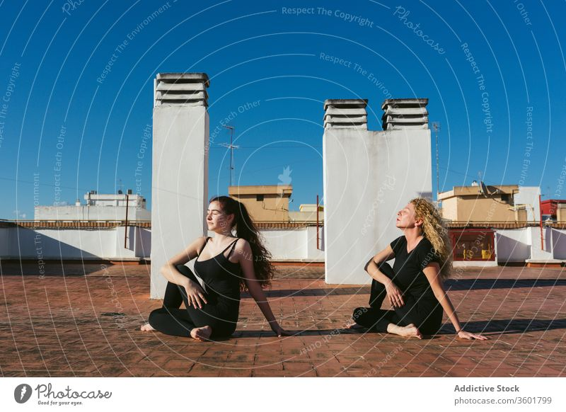 Women practicing yoga together on rooftop women terrace practice pose position ardha matsyendrasana twist half lord of the fishes acro yoga mother daughter