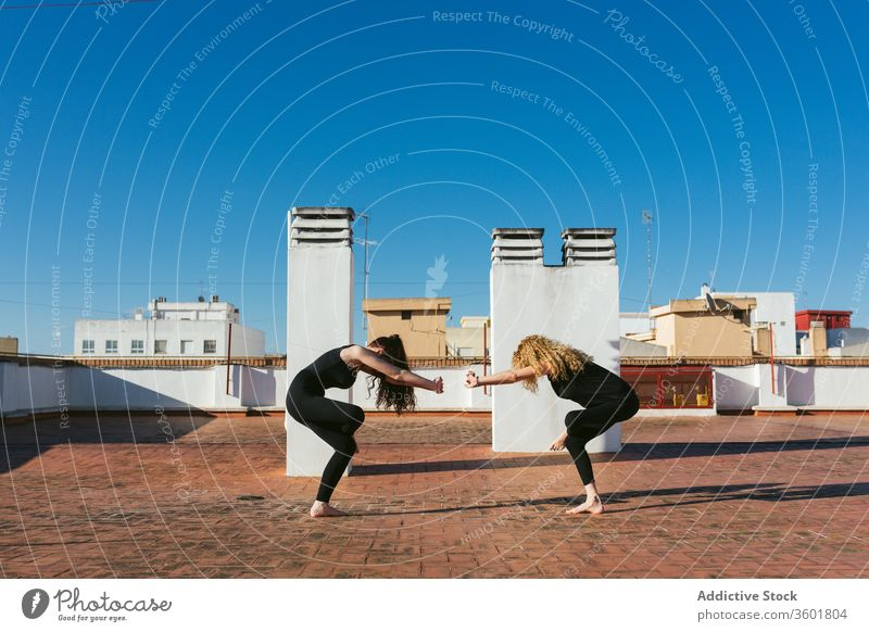 Women practicing yoga together on rooftop women terrace practice pose position twist acro yoga mother daughter lifestyle harmony relax wellness asana female