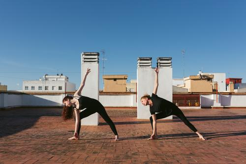 Women practicing twist yoga pose on rooftop women together practice revolved triangle parivrtta trikonasana stand position stretch balance terrace lifestyle