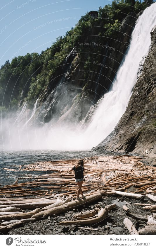 Unrecognizable lonely female teenager walking along river shore against waterfall girl beach fresh snag travel cascade nature tranquil wilderness flow rocky