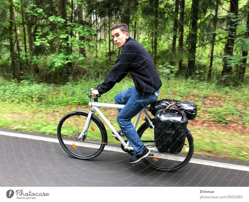 Young man on a bicycle tour younger Bicycle Cycling tour In transit Luggage family vacation active Attractive