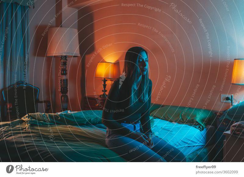 Young woman sadly sitting on the bed portrait female night quarantine depression pillow coronavirus covid-19 isolation self-isolated insomnia blue orange 30s