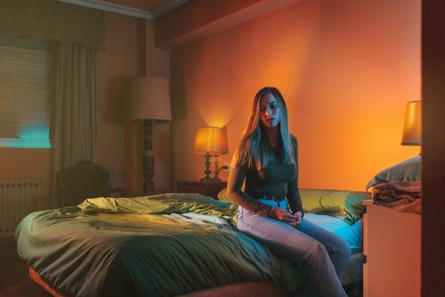 Young woman sadly sitting alone on the bed late at night portrait female quarantine depression pillow coronavirus covid-19 isolation self-isolated insomnia blue
