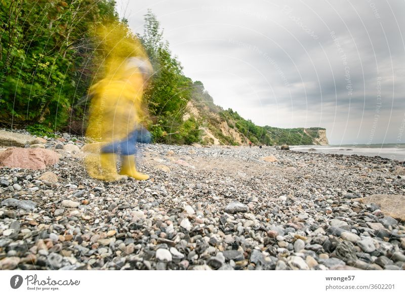 A shadowy creature in Frisian ore walks along the beach of the island of Rügen Motion blur blurred Nature Human being Child friesennerz rain shelter