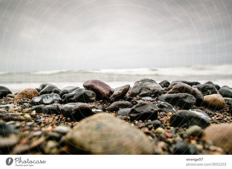 Wet shiny stones are lying on the beach in front of the towering waves of the Baltic Sea Pebble beach Glittering Lie Beach Baltic beach Waves high waves