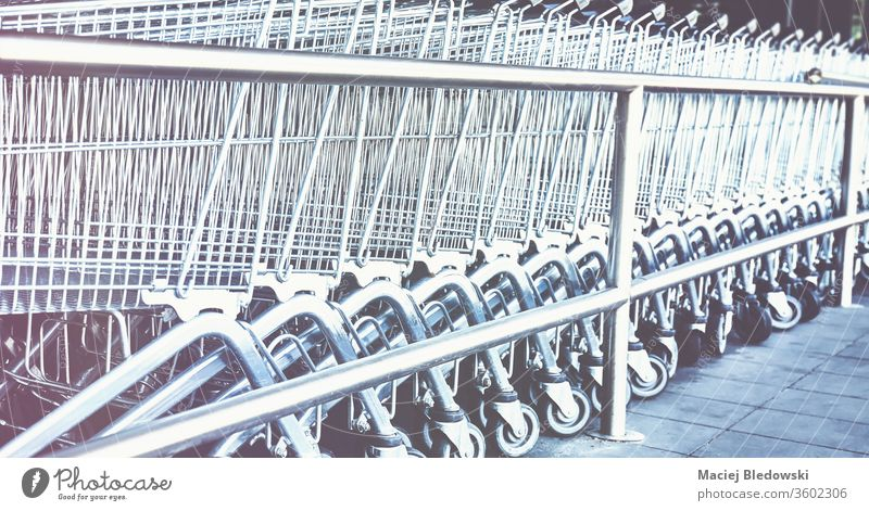 Row of empty shopping carts. supermarket retail row trolley store buy basket instagram effect business grocery consumerism metallic purchase chrome object