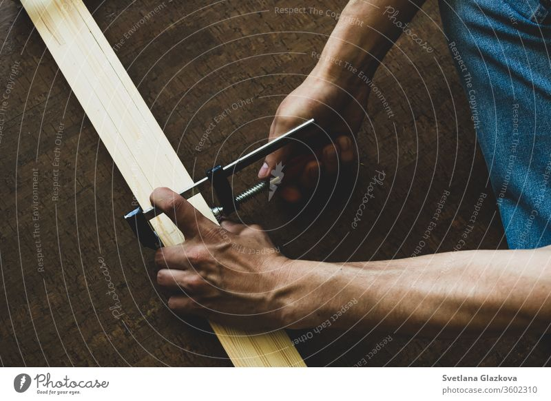 Men's hands fasten the clamp to the wooden rails, making a measurement before cutting. Repair concept tool home work repair construction industry person build