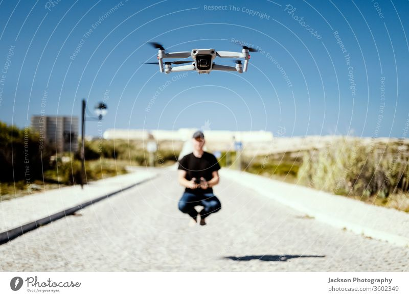 Man holding remote flying together with his drone man flight copter technology concept aladin happiness sunny road outdoor caucasian device multicopter