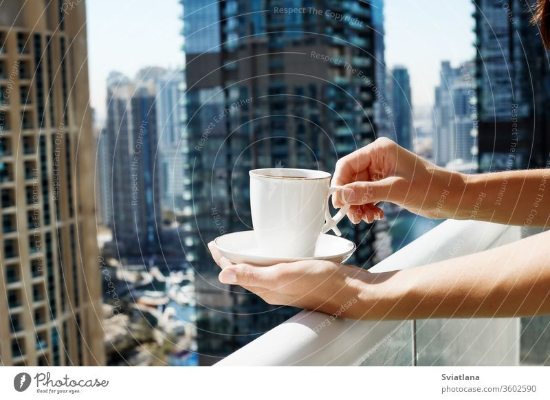 A girl holds a Cup of coffee against the background of modern buildings. A woman drinks morning coffee on the balcony during self-isolation city luxury view
