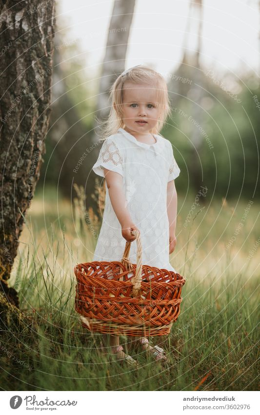 Beautiful baby girl walking in a sunny garden with a basket. little girl in a white dress with a basket in the park spring portrait kid beauty child field