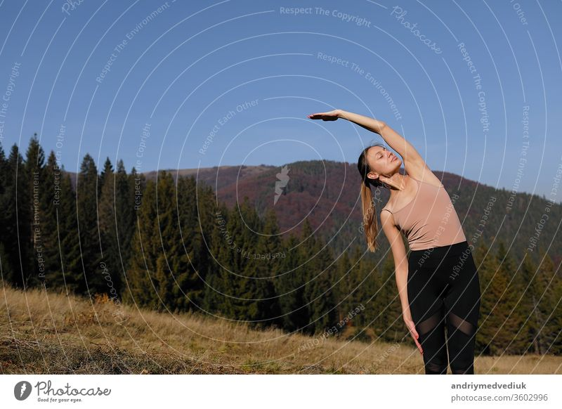 Young woman doing stretching exercises on nature in mountains. Sports girl practicing yoga pose in leggings. beautiful forest landscape zen sporty fitness stone