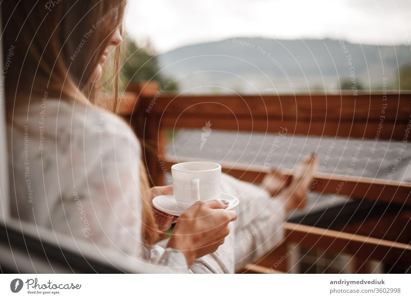 young woman in stylish nightwear enjoy drinking coffee or tea outdoor on balcony in the morning and looks at the mountains. cup home relax adult attractive