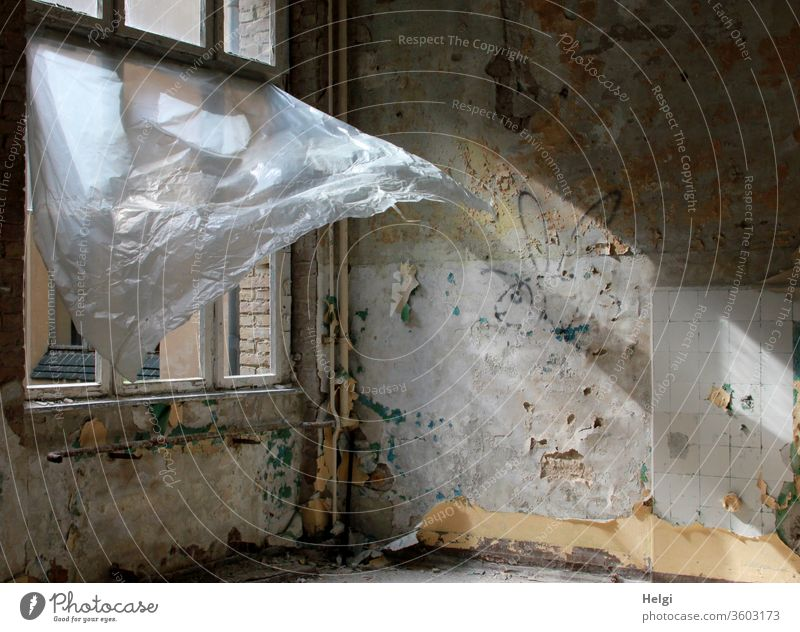 Draught - in an old dilapidated building with a destroyed window, a plastic curtain blows up from the wind and lets the sunlight in built