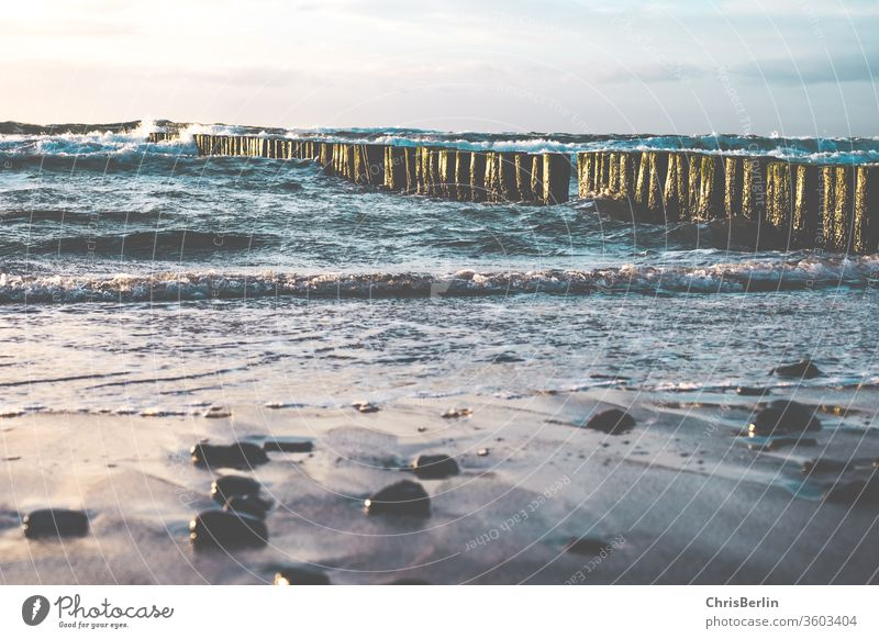 Eastern beach with waves and groynes Beach stones Waves Buhnen in the sea Gale Sunset Clouds