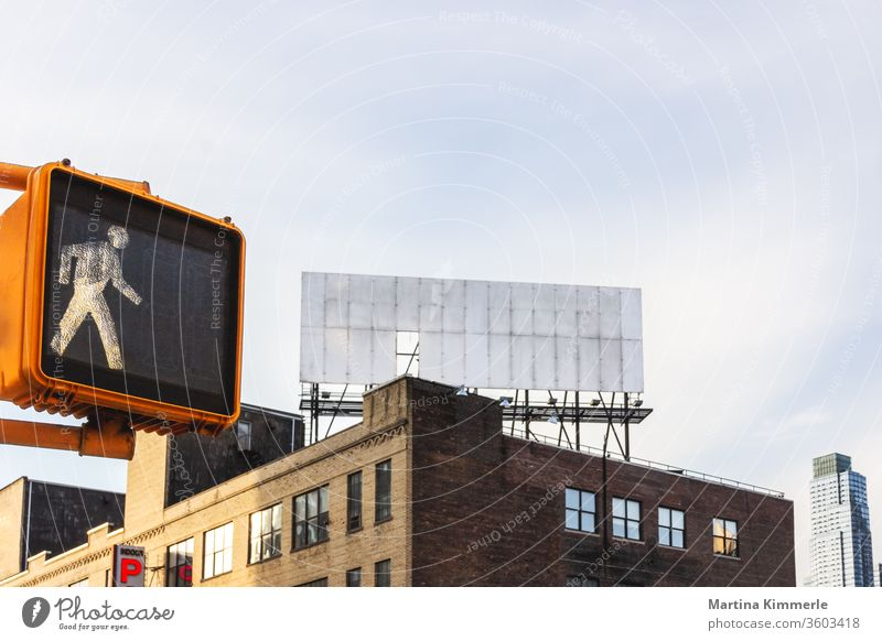 Pedestrian traffic light and empty billboard on a roof in New York City Architecture Way out on the outside office Window built Glass