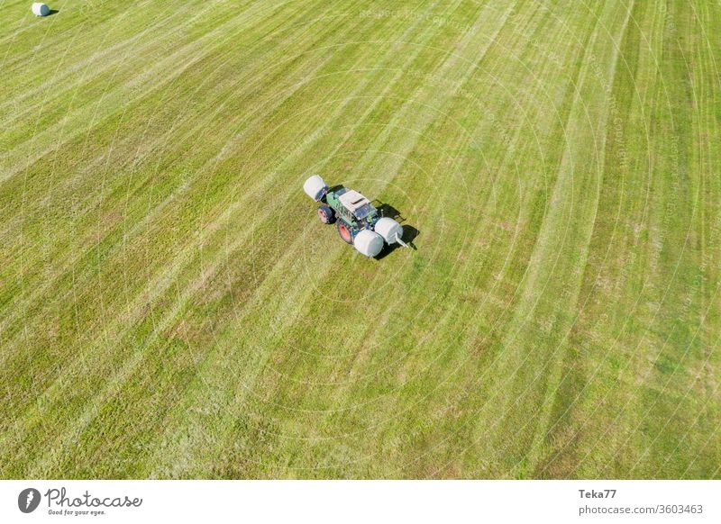 a tractor makes hay bales on a field tractor from above historic tractor making hay green tractor tractor on a field agricultural agricultural way tractor path