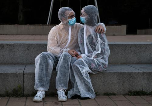 Couples cuddling in protective suits and masks Love corona Protection Protective clothing Mask proximity hug Safety sure Absurd Cuddling detachment pandemic