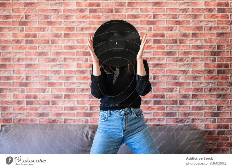 Anonymous young woman holding a black vinyl with her hands beautiful girl music disco female fashion sound background portrait person audio people entertainment
