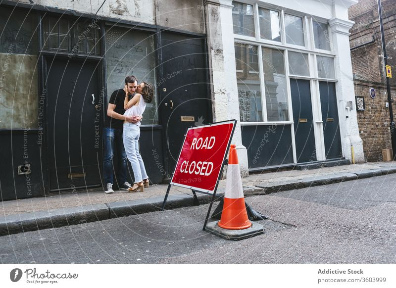 Cheerful couple hugging and kissing on street stroll city tender shabby building roadside london england united kingdom date together embrace love relationship