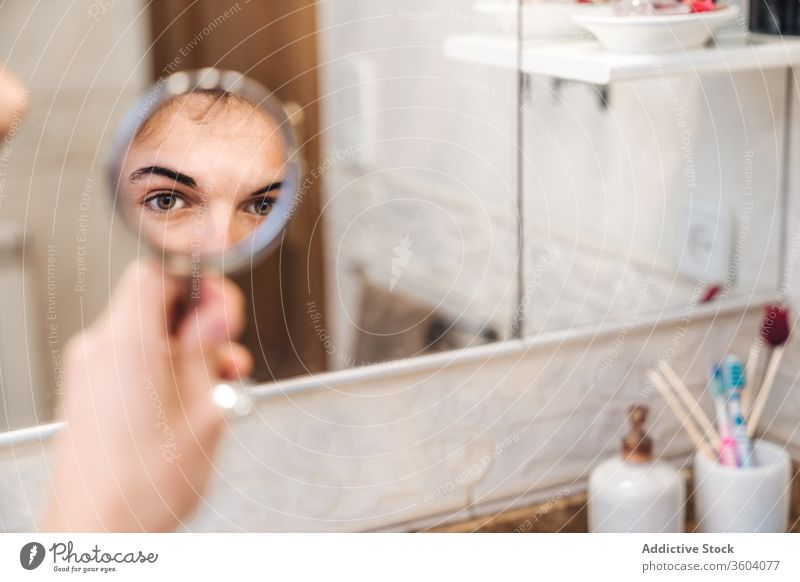 Handsome man looking in mirror bathroom eyes morning home bright serious routine daily fresh male stand hygiene style care clean contemporary modern healthy