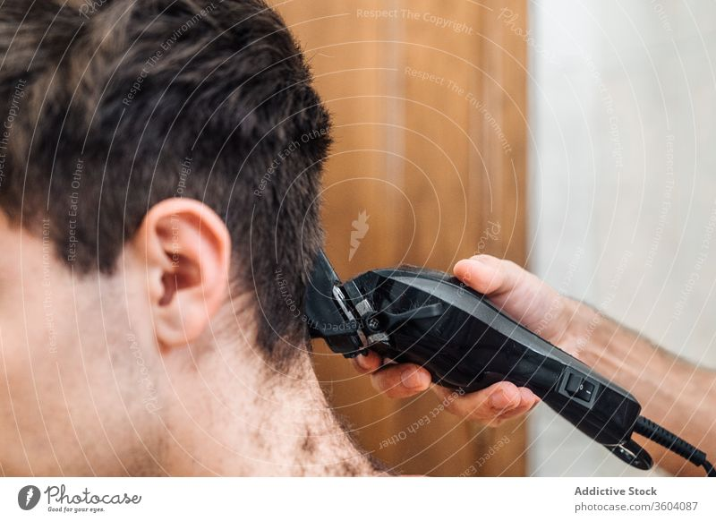 Crop barber doing haircut for man trimmer bathroom men grooming together hairdresser contemporary modern tool hygiene care routine beauty friendship hairstyle