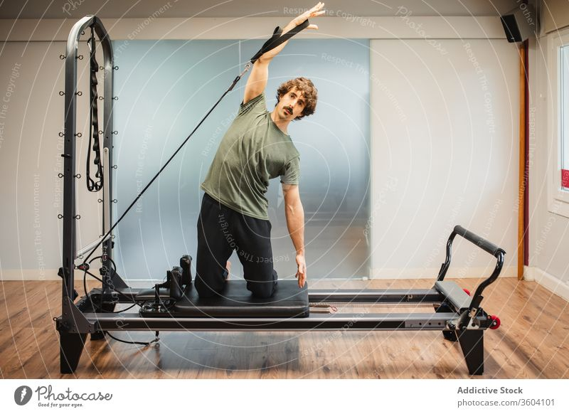 Sportive man using pilates reformer during training stretch sporty activewear resist band machine sportsman athlete exercise workout fitness healthy sportswear