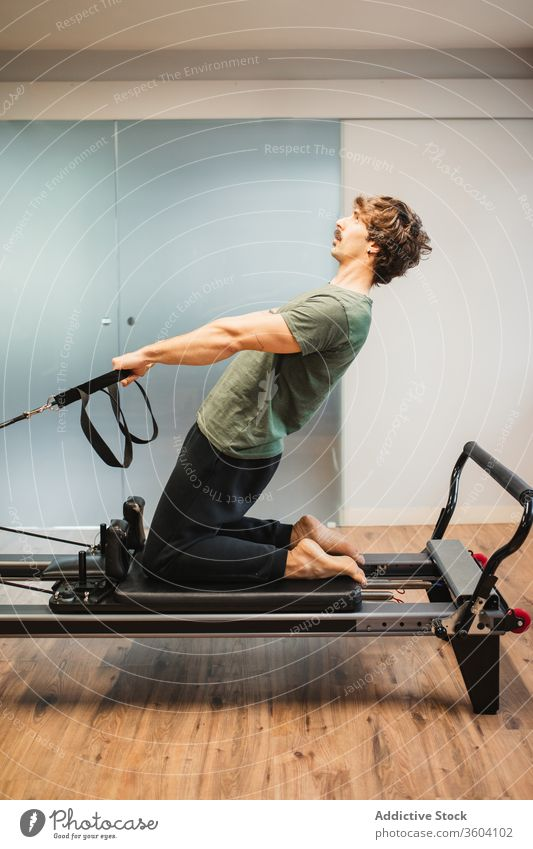 Sportive man using pilates reformer during training stretch sporty activewear resist band machine male sportsman athlete exercise workout fitness healthy