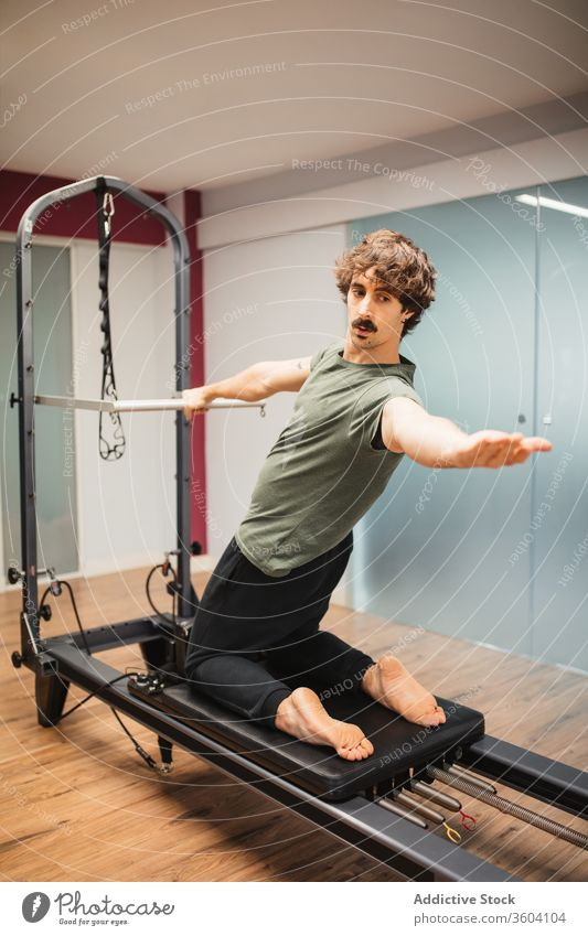 Sportsman using pilates machine reformer sportsman exercise training workout sportswear gym healthy lifestyle athlete male power wellness strong physical effort