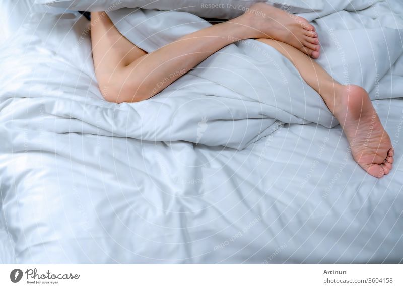 Close up woman bare feet on the bed  over white blanket and bed sheet in the bedroom of home or hotel. Sleeping and relax concept. Lazy morning. Barefoot of woman lying on white comfort bed and duvet.