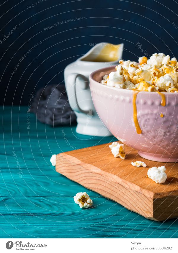 Popcorn with caramel in bowl on dark background popcorn sauce sweet cooked food snack crunchy salty delicious studio tasty ceramic salted cereal jar fluffy