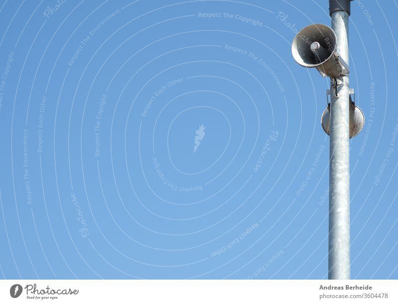 Loudspeakers on a lamppost against a blue summer sky loudspeaker broadcast steel communication urban siren streetlight streetlamp security warning sound space