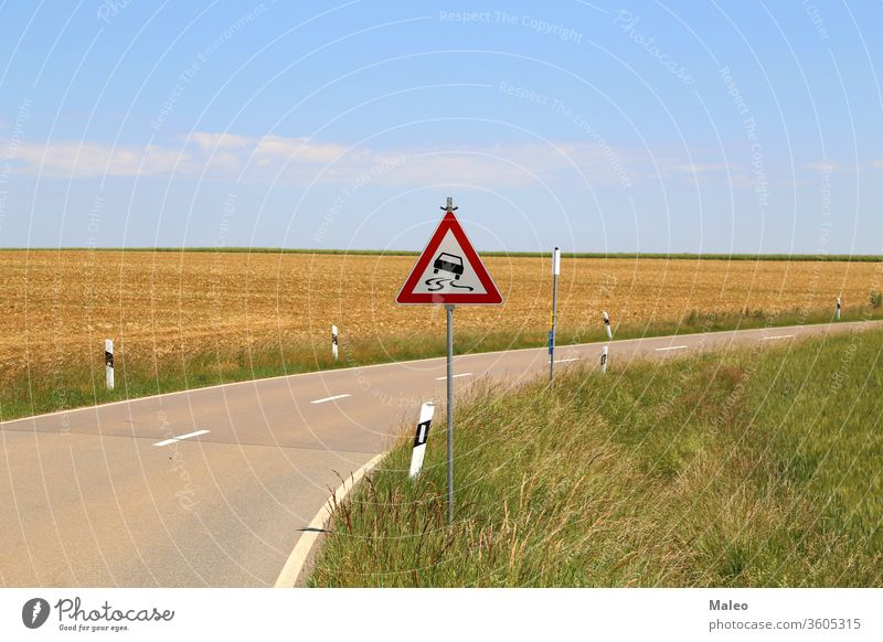 Slippery road - Road sign stands on a sharp turn slippery curve danger traffic dangerous winding warning arrow caution street travel yellow alert drive highway