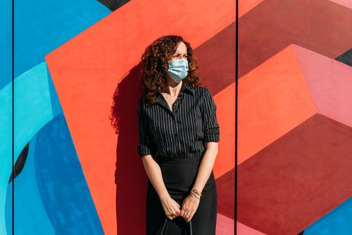 Woman with face mask in front of a wall with bright colors. epidemic people coronavirus woman protection flu covid-19 sick disease health street infection