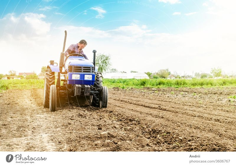 Farmer is processing soil on a tractor. Soil milling, crumbling mixing. Loosening surface, cultivating land for further planting. Agriculture, growing organic food vegetables. Agroindustry, farming.