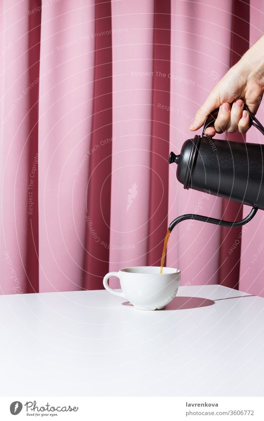 Woman's hand holding black metal pot and pouring coffee or tea into white cup in front of pink drapery, selective focus beverage morning drink mug breakfast