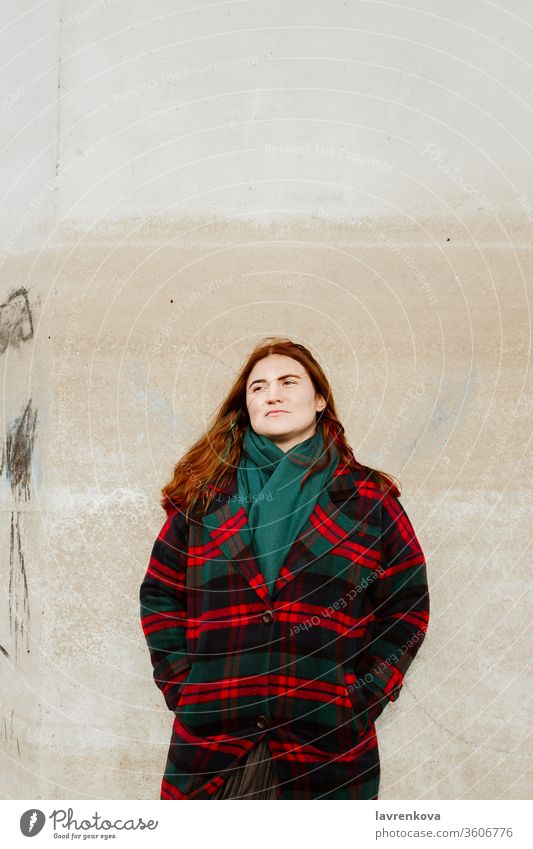 Female with red hair in plaid coat standing outdoors woman female autumn alone lifestyle adult checked wall Looking away season winter candid portrait redhead