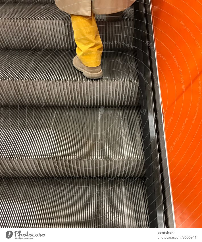 Bright yellow trouser leg meets bright orange side wall of an escalator. Fashion and style. Being on the move bright-coloured Escalator garments Yellow Orange