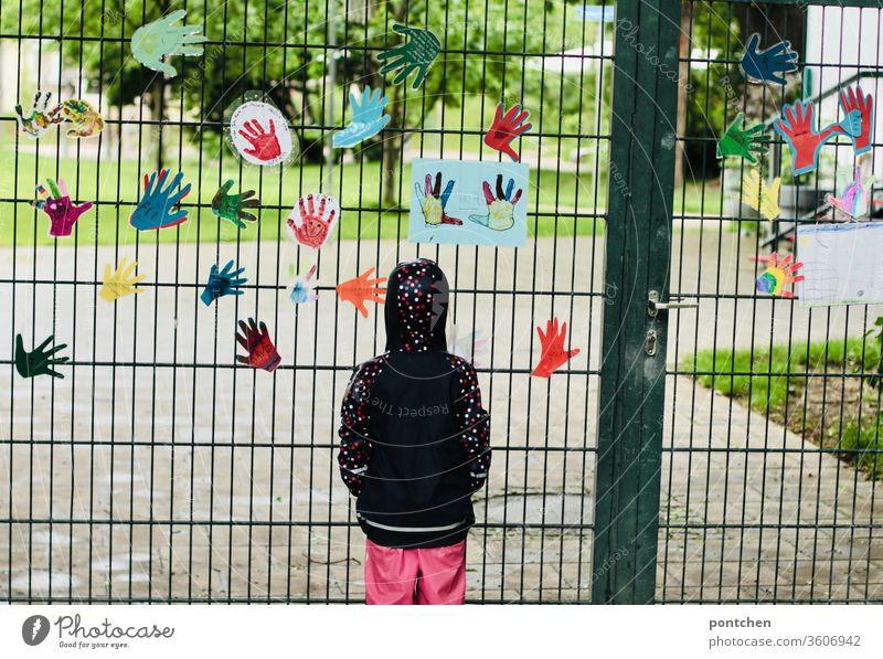 A child in rainwear stands sadly in front of a closed kindergarten.  exit restrictions, corona, closures Child Longing Kindergarten Closed hands Goal Garden